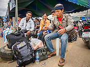 09 JULY 2014 - ARANYAPRATHET, SA KAEO, THAILAND: Cambodian migrant workers wait to go into the Thai Immigration One Stop Service Center in Aranyaprathet on the Thai-Cambodian border. More than 200,000 Cambodian migrant workers, most undocumented, fled Thailand in early June fearing a crackdown by Thai authorities after a coup unseated the elected government. Employers have been unable to fill the vacancies created by the Cambodian exodus and the Thai government has allowed them to return. The Cambodian workers have to have a job and their employers have to vouch for them. The Thai government is issuing temporary ID cards to allow them to travel openly to their jobs. About 800 Cambodian workers came back to Thailand through the Aranyaprathet border crossing Wednesday. The Thai government has opening similar service centers at three other crossing points on the Thai-Cambodian border.    PHOTO BY JACK KURTZ