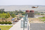 Israeli Air Force (IAF) helicopter, Sikorsky UH-60 Blackhawk (Yanshuf) in flight over the recently restored Ottoman railway station at Tzemach (Samakh) on the southern shores of the Sea of Galilee, Israel (Inaugurated in 1905)