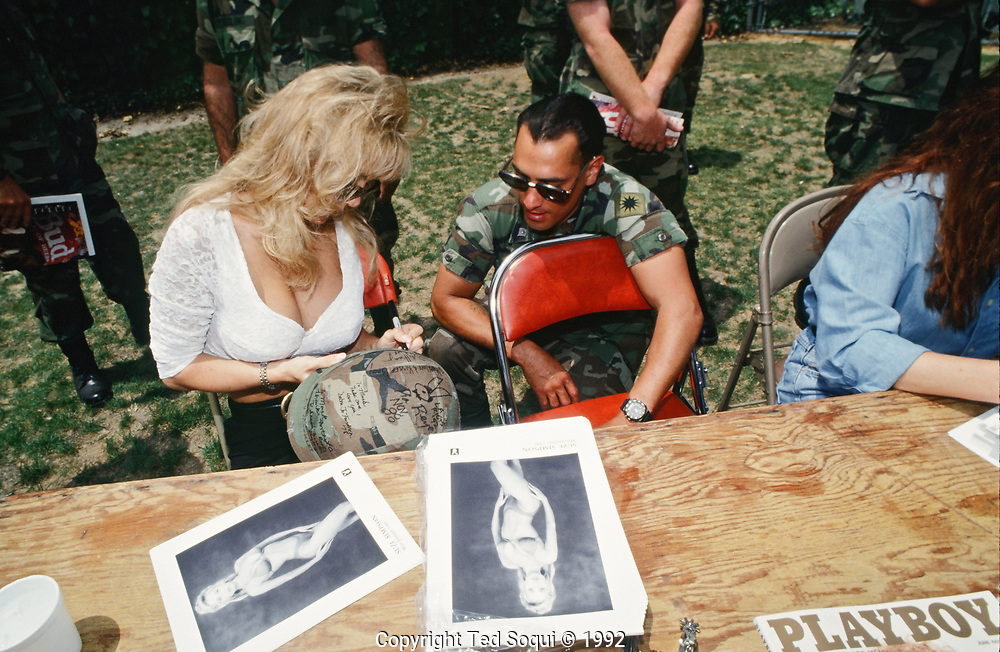 Playboy Playmates sign autographs for National Guard soldiers posted near the Coliseum in Los Angeles.