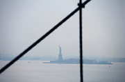 Statue of Liberty in New York City harbor with the cables of the Brooklyn Bridge in the foreground
