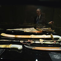 """TREVISO, ITALY - NOVEMBER 12:  Curator Adriano Madaro looks at some swards and daggers belonging to the Manchu Army called """"Eight Banners"""" at the Case dei Carraresi on November 12, 2011 in Treviso, Italy.  The exhibition called, """"Manchu, The Last Emperor"""" will stay open until the 13th May 2012.  (Photo by Marco Secchi/Getty Images)"""