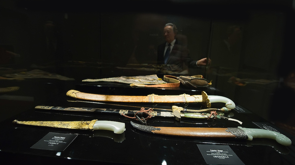 "TREVISO, ITALY - NOVEMBER 12:  Curator Adriano Madaro looks at some swards and daggers belonging to the Manchu Army called ""Eight Banners"" at the Case dei Carraresi on November 12, 2011 in Treviso, Italy.  The exhibition called, ""Manchu, The Last Emperor"" will stay open until the 13th May 2012.  (Photo by Marco Secchi/Getty Images)"