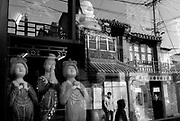 Beijing, China - November 26, 2005 - A street scene reflected in the window of an antique shop selling Tang Dynasty figurines in Beijing. Photo by Natalie Behring