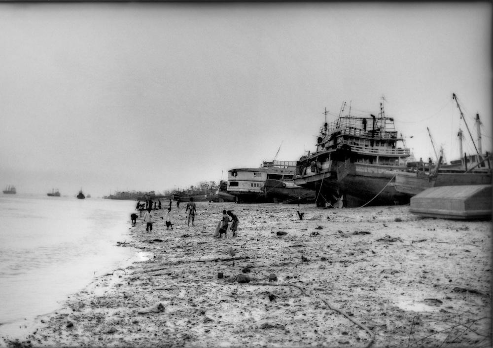 Ships left beached by Cyclone Nargis line bank of Yangon River the morning after the storm, Dalah, Burma (Myanmar).
