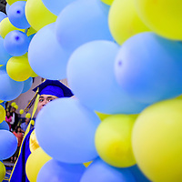 052215       Cable Hoover<br /> <br /> Alliah Soseeah peeks through an archway of balloons as he marches into the gymnasium for graduation Friday at Zuni High School.