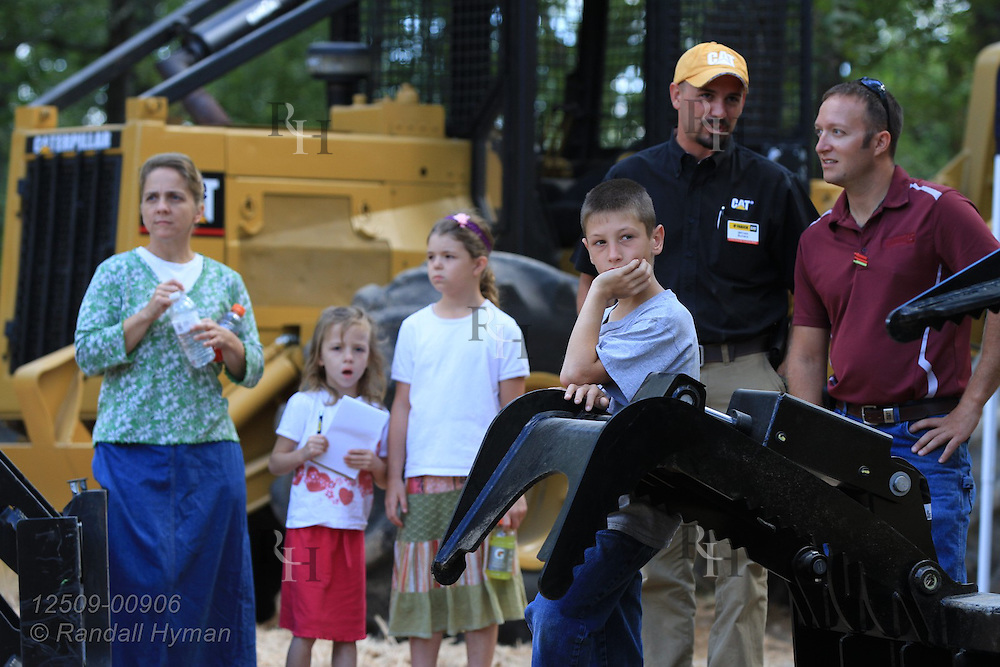 Family watches ultra-mechanized clearcutting of an Ozarks woodland at Missouri In Woods Logging Demo near Viburnum, Missouri.