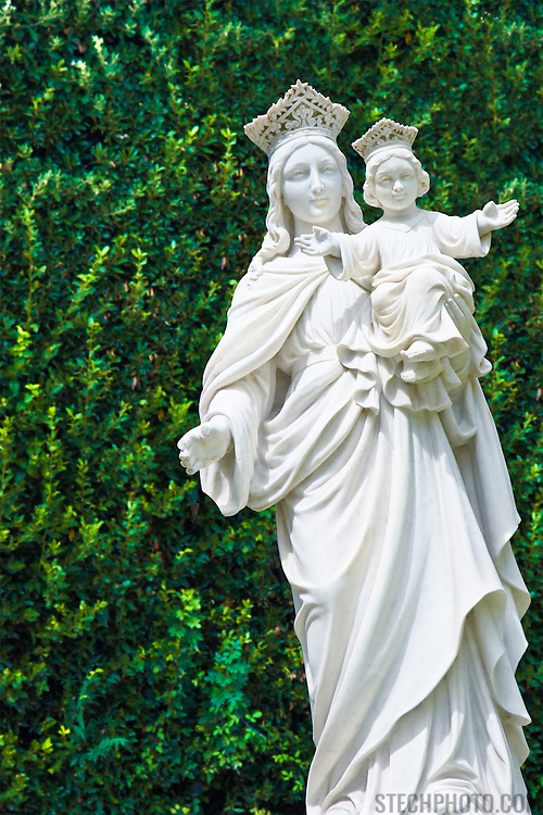 A statue of Mary and Jesus Christ in front of a large bush in the town of Gorizia, Italy.