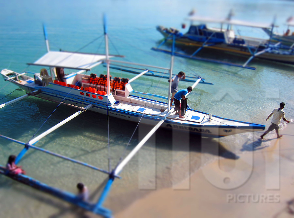 Young men prepare pump boat on shore of El Nido, Palawan, Philippines, Southeast Asia