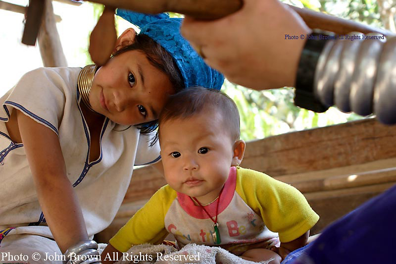 A Karen Paduang refugee family enjoys music outside their home at a refugee camp in Ban Nai Soi, Thailand. Over 75,000 people are now residing in Northern Thailand after fleeing war atrocities in their homeland of Burma (Myanmar). The Karen Paduang people are considered a tourist attraction in Thailand.