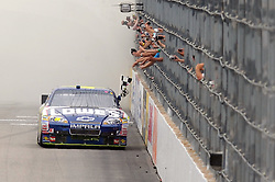 LOUDON, NH - JUNE 27:  Jimmie Johnson, driver of the #48 Lowe's Chevrolet, celebrates with the checkered flag after winning the NASCAR Sprint Cup Series LENOX Industrial Tools 301 at New Hampshire Motor Speedway on June 27, 2010 in Loudon, New Hampshire.  (Photo by Drew Hallowell/Getty Images for NASCAR) *** Local Caption *** Jimmie Johnson