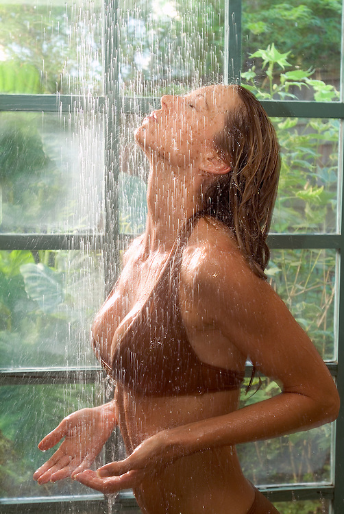 Wellness image of young woman in brown bikini rinsing off in shower.