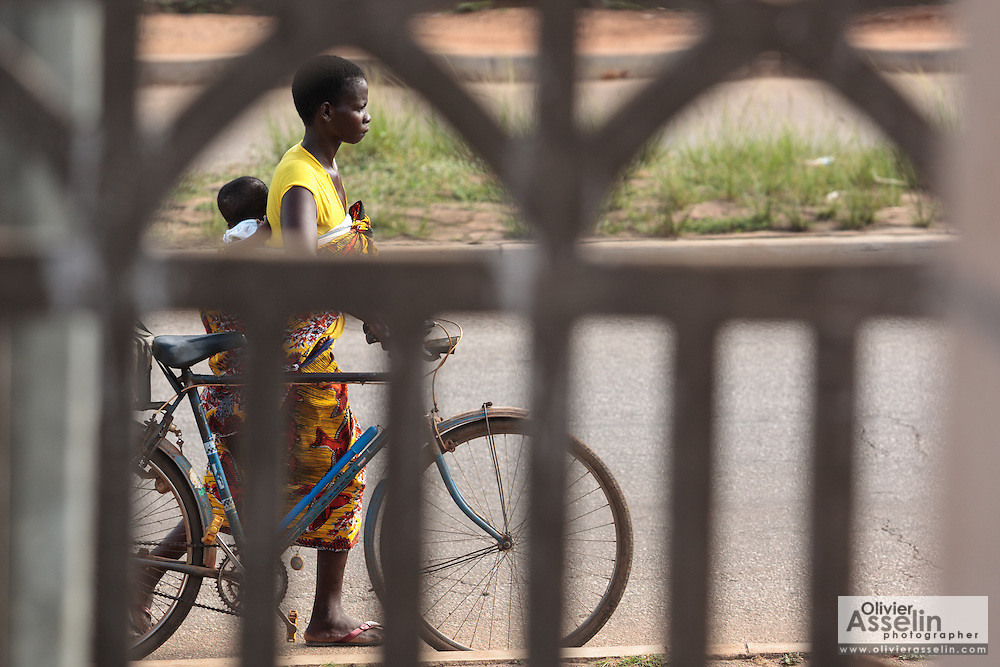 A woman carrying a child on her back pushes her bicycle as she walks down the main road in Katiola, Cote d'Ivoire on Saturday July 13, 2013.