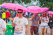 The pink brolloies are in tribute to a 'secret' facebook group attending the festival. As usual, the rain begins to fall and fails to dampen spiriits. The 2014 Glastonbury Festival, Worthy Farm, Glastonbury. 26 June 2013.  Guy Bell, 07771 786236, guy@gbphotos.com
