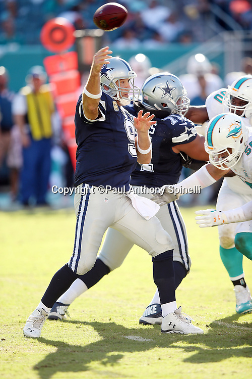 Dallas Cowboys quarterback Tony Romo (9) throws a third quarter pass for a first down as he gets ready to take a hit from a defender during the 2015 week 11 regular season NFL football game against the Miami Dolphins on Sunday, Nov. 22, 2015 in Miami Gardens, Fla. The Cowboys won the game 24-14. (©Paul Anthony Spinelli)