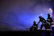 Hutchinson fire fighters spray a stream of water on Midwest Sewing and Nelson Heating & Air Conditioning building at 211 West Fifth Friday, Jan. 17, 2015 as they work to extinguish a fire in the building.