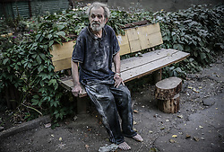 A wounded local man sits near damaged block of flats after Ukranian army shelling in downtown of Donetsk, Ukraine, 23 August 2014. Residential areas in several districts of Donetsk, including the central part of the city, suffered from artillery fire, five people was killed and 15 wounded, the press centre of Donetsk city Council reported.