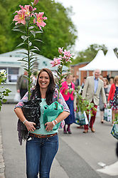 © London News Pictures. 23/05/2015. London, UK. Natalie Miller with the flowers she bought. Members of the public carry exhibitors' plants from the 2015 Chelsea Flower show, which ends today (Sat). The Royal Horticultural Society flagship flower show has been held at the Royal Hospital in Chelsea since 1913. Photo credit: Ben Cawthra/LNP