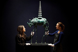 © Licensed to London News Pictures. 31/01/2013. London, UK. Two Bonhams employee adjust 'Chair de poule rhinocerontique, ou Rhinoceros cosmique' (conceived in 1956) (est. GB£150,000-250,000) a bronze sculpture by Spanish surrealist Salvador Dali at the press view for the Bonhams' Impressionist and Modern Art Sale in London today (31/01/13). The sale, to be held at the London based auction house's New Oxford Street premises on the 5th of February, features a selection of eclectic artists including Camille Pissarro, Fernand Leger and Edgar Degas. Photo credit: Matt Cetti-Roberts/LNP