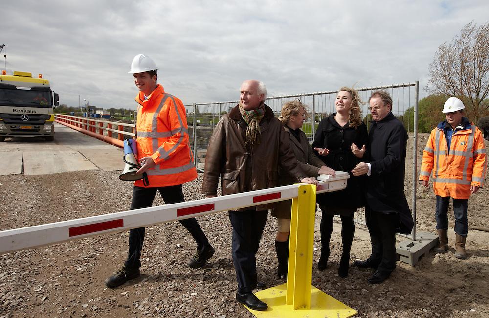 Nederland. Vlaardingen, 26 april 2012.<br /> Met de opening van de slagboom op de hulpbrug voor het bouwverkeer bij het Kethelplein in Vlaardingen heeft minister Schultz van Haegen (Infrastructuur en Milieu) vandaag het startschot voor de aanleg van de A4 Delft-Schiedam gegeven. De 7 kilometer lange weg is de ontbrekende schakel op de A4 tussen Den Haag  en Rotterdam. &ldquo;Dit meest besproken stukje weg van Nederland is cruciaal voor een betere bereikbaarheid in de regio en daarmee voor de economie&rdquo;, aldus minister Schultz van Haegen. <br />  <br /> De A4 Delft-Schiedam gaat de overvolle A13 ontlasten en vermindert de overlast van  sluipverkeer op lokale wegen. De reistijd tussen Den Haag en Rotterdam zal flink afnemen. Bovendien wordt het netwerk robuuster, omdat er bij een ongeval of werkzaamheden een alternatieve route is. Op een gemiddelde werkdag zullen circa 128.000 motorvoertuigen per etmaal gebruik maken van de A4 Delft-Schiedam.  <br />  De weg, die in 2015 wordt opengesteld voor het verkeer, krijgt een verdiepte ligging en een tunnel. Daarbij krijgt het gebied een kwaliteitsimpuls. Er wordt ge&iuml;nvesteerd in de verbetering van de kwaliteit van dit groene gebied met de aanleg van 100 hectare natuur, ecoducten, de sanering van glastuinbouw, de aanleg van ruiter- en wandelpaden, waterberging en duurzame landbouw. Met de aanleg van de weg en de kwaliteitsimpuls van het gebied is 650 miljoen euro gemoeid.  <br /> Foto : Martijn Beekman