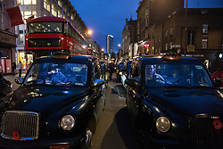 London, UK. 21st January, 2019. Licensed taxi drivers, or black cab drivers, block Tottenham Court Road in protest against a ruling by Camden Council that taxis, lorries and cars will be banned from the road from 8am-7pm on Monday to Saturday with effect from March 2019. The road, and nearby Gower Street, will also be transformed from one-way to two-way traffic.