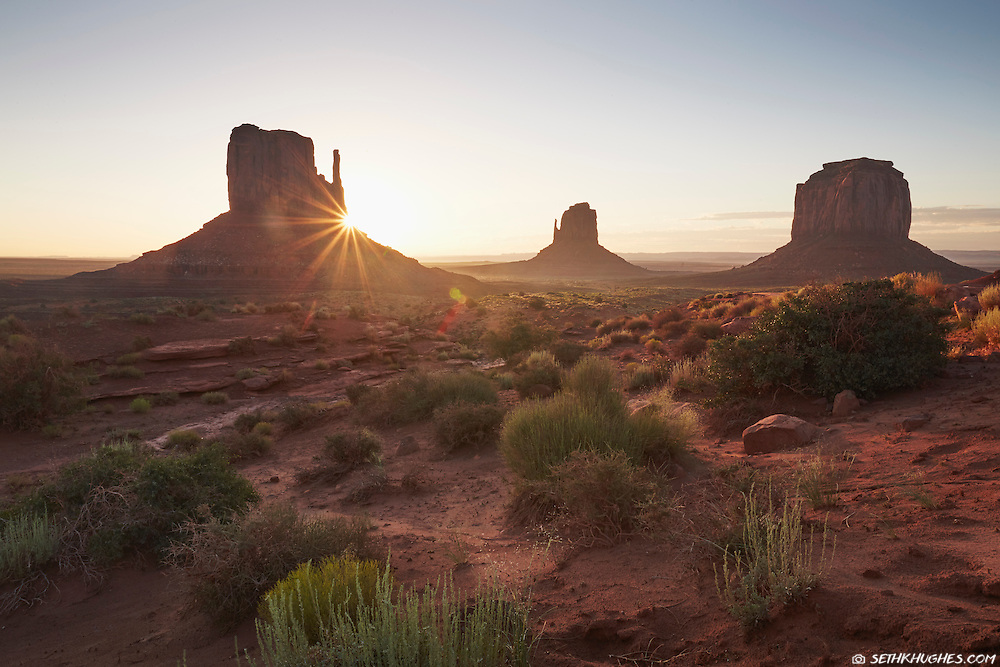 The sun rises behind a famous rock formation in Monument Valley, Arizona.