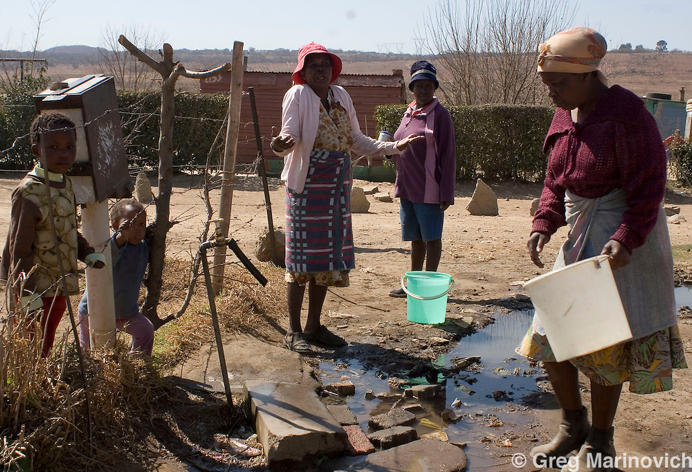 People of Boiketlong collect water from a communal standpipe. Residents of the informal settlements that dot the Sebokeng/Evation area south of Johannesburg have been taking to the streets to protest lack of service delivery, or inadequate services that are not what they believe were promised them by the African National Congress before they came into power in 1994. August 24, 2007. Photo Greg Marinovich