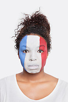 Portrait of sad young African American woman with French flag painted on face against white background