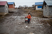 Ivan Kaleja (26) and his wife Klara (22) with their new born child coming home from a walk back to the settlement where they life in. The village of Ostrovany, located about 50 km from Kosice in the Sabinov district, shows the difficulties experienced by the minority and majority population living together in one village. A wall was erected in 2009 to divide private properties from the neighbouring Roma settlement. In the settlement are living 304 children aged between 0-6 years, compared to the village, with 37 inhabitants in this age group. (2013)