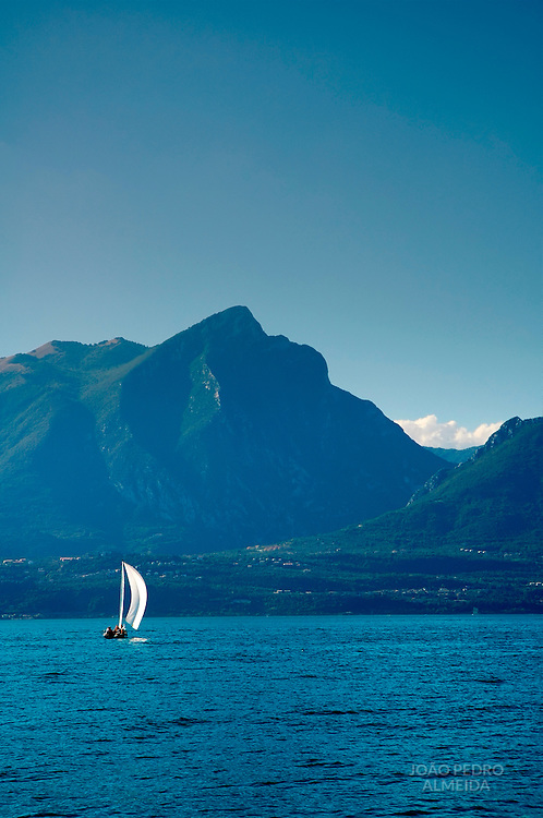 Sailboat at Lake Garda with mountains on the back