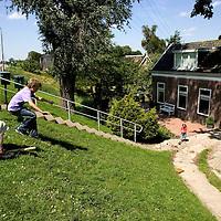 Nederland Lekkerkerk 30 mei 2007 20070527.Kinderen proberen te sleeen snowboarden van dijk ..Serie tbv Schieland en de Krimpenerwaard, deze zorgt als waterschap voor droge voeten en schoon water in een bepaald gebied. Het beheersgebied van Schieland en de Krimpenerwaard strekt zich uit tussen Rotterdam, Schoonhoven en Zoetermeer. Binnen dit gebied zorgt Schieland en de Krimpenerwaard voor de kwaliteit van het oppervlaktewater, het waterpeil en de waterkeringen. Daarnaast beheert Schieland en de Krimpenerwaard een aantal wegen in de Krimpenerwaard...Foto David Rozing