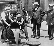 Prohibition in the USA 1920-1933: A barrel of confiscated illegal beer being poured down a drain. Alcohol Temperance  America