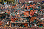 Lobster traps. St. Martins, in Saint John County, New Brunswick, Canada. Observe the extreme tides of Bay of Fundy lifting fishing boats near the bridge. Drive through the covered bridge and go 7 km on Big Salmon River Road to reach the start of the Fundy Trail Parkway, a 16 kilometer auto route along the Fundy coast ending at Big Salmon River, a former lumbering center. Bay of Fundy has the highest tidal range in the world, due to a resonance of being just the right length (270 km) matching the gravitational pushing cycle of the Moon that causes the tides. Coincidentally, the time it takes a large wave to go from the mouth of the bay to the inner shore and back is practically the same as the time from one high tide to the next. (You can see the effect of resonance for yourself by steadily pushing a long pan of water back and forth: an optimal pushing frequency for a given pan length will build up a high wave of water which sloshes out; but pushing too fast or too slow won't build up the big wave.) Two high tides occur per day, one when the ocean side is nearest the Moon, and one on the side of the Earth most distant from the Moon, about 12 hours and 25 minutes from one high tide to the next. The Bay of Fundy is on the Atlantic coast of North America, on the northeast end of the Gulf of Maine between the Canadian provinces of New Brunswick and Nova Scotia. St. Martins (2006 population: 386) is 40 km east of Saint John. St. Martins (originally known as Quaco) was founded by Loyalists in 1783. Its important 1800s shipbuilding center faded, leaving tourism as today's major industry.