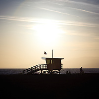 Santa Monica California beach lifeguard stand sunset over the Pacific Ocean at Santa Monica State Beach Park in Los Angeles County Southern California.