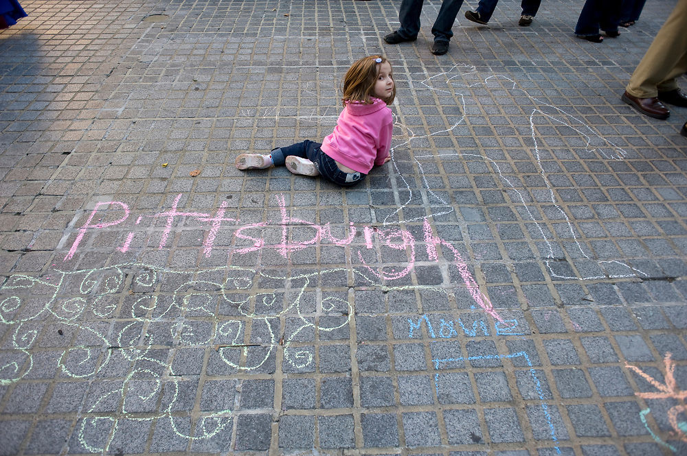Elena DiNitto, age 5, of New Kensington, pauses while drawing on Katz Plaza during the Pittsburgh Cultural Trust Fall Gallery Crawl in downtown Pittsburgh.