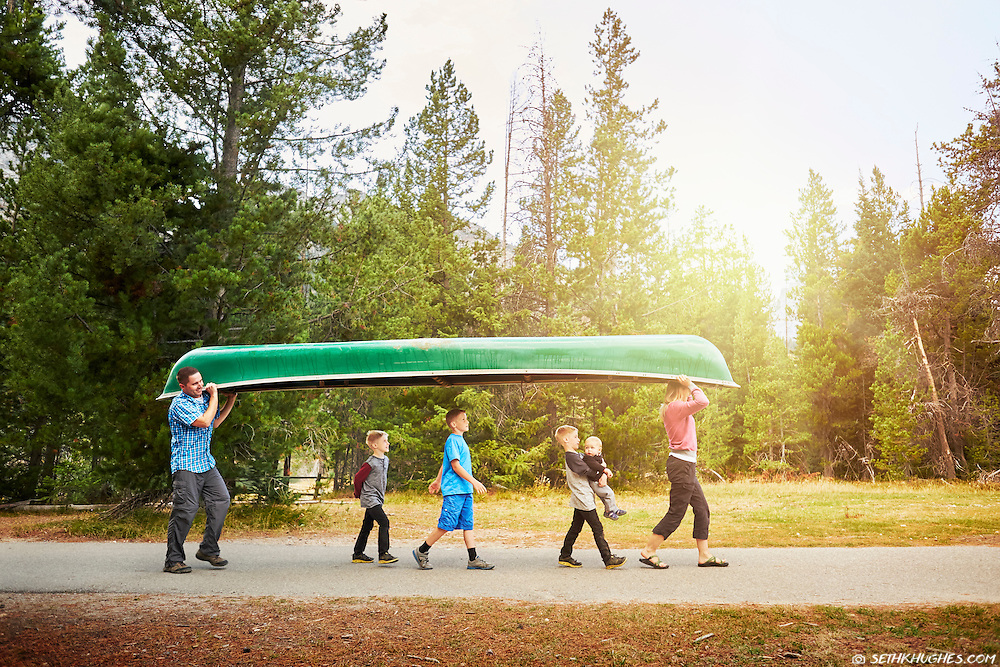 A family uses teamwork to carry their canoe to the water's edge at Jenny Lake, GTNP, WY.