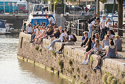 © Licensed to London News Pictures; 13/09/2020; Bristol, UK. People sit on the harbour wall enjoying sunshine and hot weather at Bristol Harbourside on the last weekend before new restrictions for the coronavirus covid-19 pandemic come into law in England. From Monday 14 September it will be illegal to meet up in groups of more than six people, known as the rule of six, in order to try and contain the spread of the coronavirus. Bristol recently recorded the biggest daily increase in 10 weeks of new cases of coronavirus, and nationally, 3,539 new cases have been confirmed, the highest rise for four months. Photo credit: Simon Chapman/LNP.