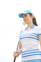 Confident woman looking away while holding golf club against clear sky