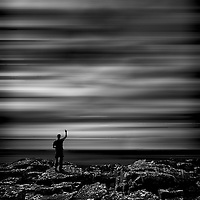 Lone figure with arm raised, looking out to sea on rocky outcrop.