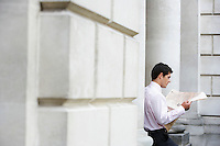 Businessman sitting on pillar reading newspaper outside building