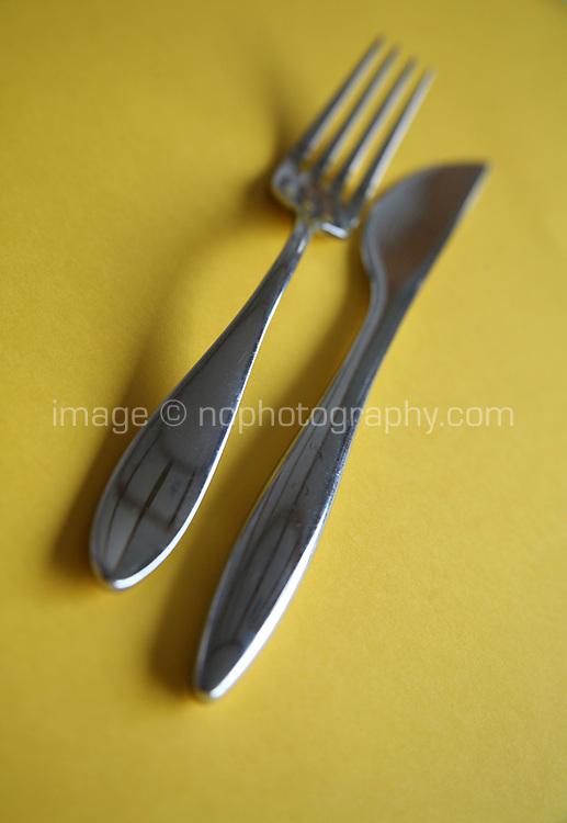 Knife and fork on colourful yellow background