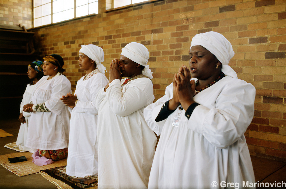 Dube, Soweto, Johannesburg, South Africa, 1990-3. Members of the Nazareth Baptist Church pray in the Zulu dominated Dube Hostel, Soweto.