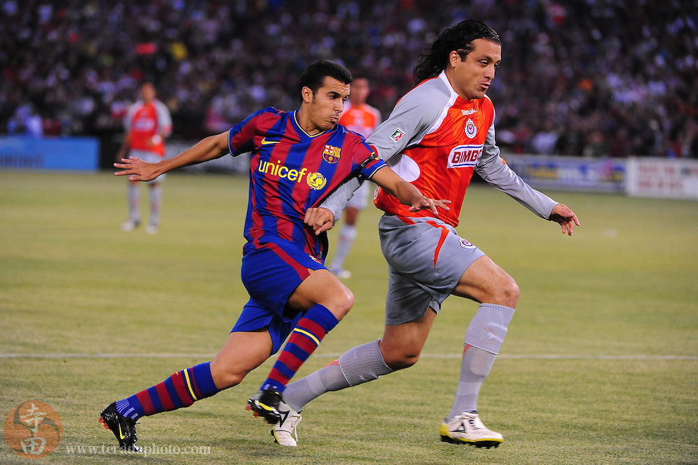 August 8, 2009; San Francisco, CA, USA; FC Barcelona defender Pedro Rodriguez (27, left) runs against Chivas de Guadalajara defender Hector Reynoso (4, right) during the first half in the Night of Champions international friendly contest at Candlestick Park.