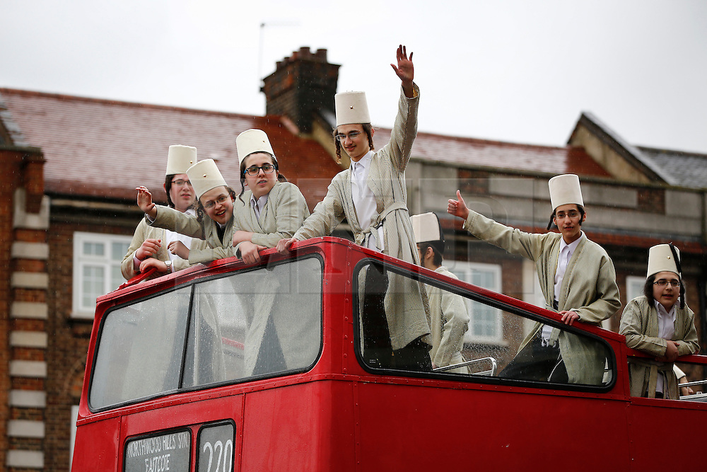 © London News Pictures. 24/03/2016.  A group of young Orthodox Jewish men ride on the top of a red bus as they  celebrate the festival of Purim in the streets of Stamford Hill in north London. Purim celebrates the miraculous salvation of the Jews from a genocidal plot in ancient Persia, an event documented in the Book of Esther. Traditionally the jewish community wear fancy dress and exchange reciprocal gifts of food and drink. Photo credit: Tolga Akmen/LNP