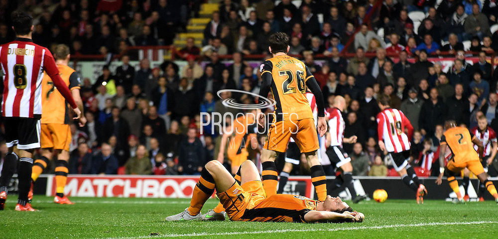 Alex Bruce lays injured as the match unfolds during the Sky Bet Championship match between Brentford and Hull City at Griffin Park, London, England on 3 November 2015. Photo by Michael Hulf.