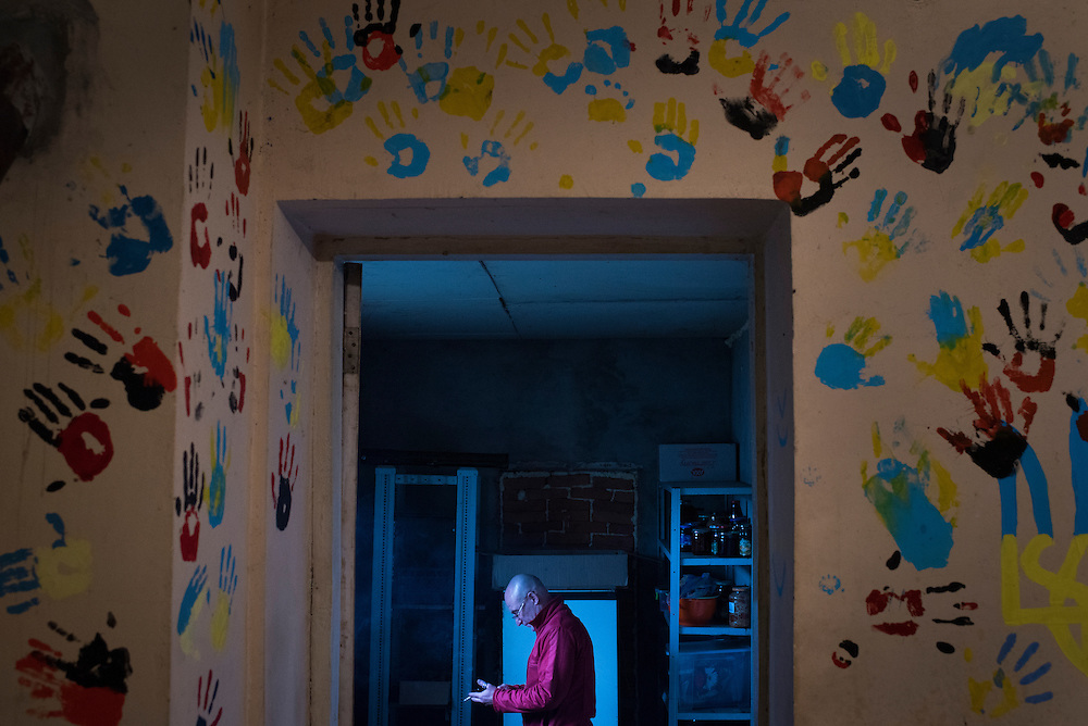Ukrop Dental founder Igor Yaschenko checks his phone in a storage room off the kitchen at his clinic on September 22, 2016 in Karlivka, Ukraine about 12km from the front line. Each dentist that volunteers in the clinic leaves their hand-print on the wall in blue and yellow (the colours of the Ukrainian flag) or black and red (nationalist colours that date to the Second World War and are used by the country's contemporary nationalist paramilitary, Right Sector).