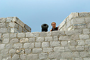 Child (9 years old) looking over stone wall parapet, beside cannon. Fortress Lovrinjenac (Fort of Saint Lawrence), Dubrovnik old town, Croatia