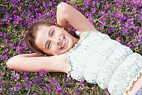 Smiling Pre-teen girl lying arms behind head in field of flowers overhead view