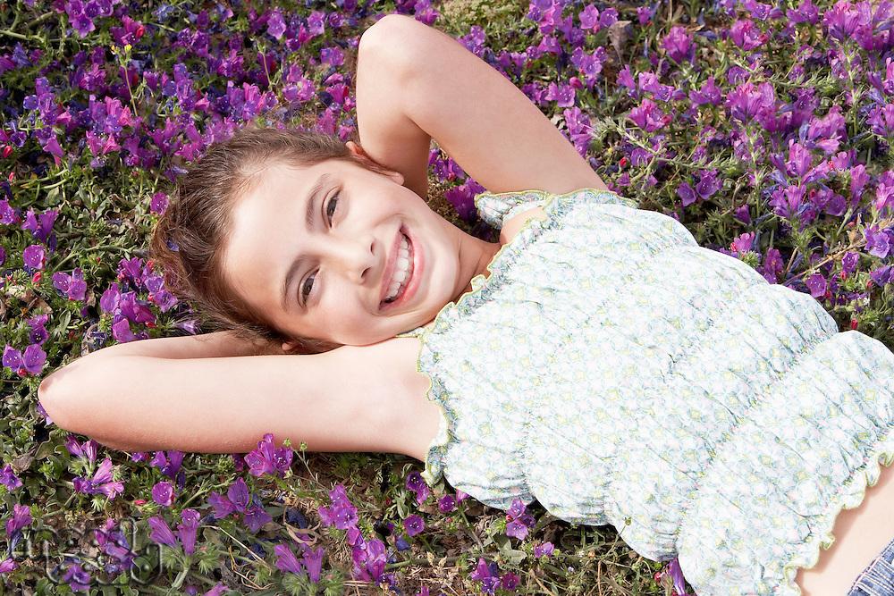Smiling Pre-teen girl lying arms behind head in field of flowers overhead view