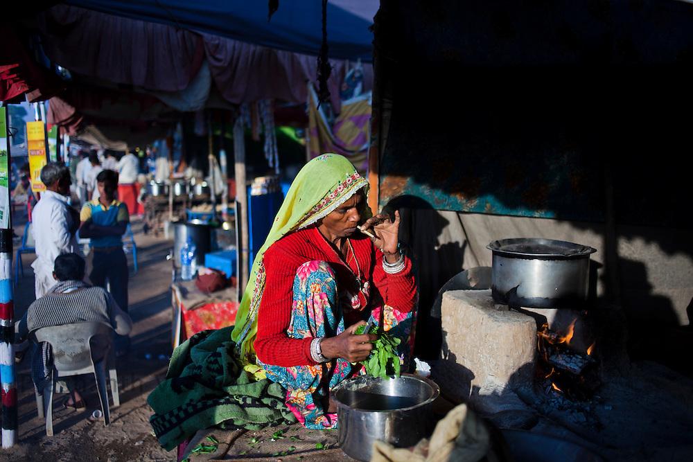 A woman cooks at a stall at the fair grounds in Pushkar, India, November 6, 2011.  Photographer: Prashanth Vishwanathan