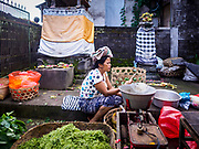 07 AUGUST 2017 - BEBANDEM, BALI, INDONESIA: A woman puts away her supplies at the end of the selling day in the market in Bebandem, in far eastern Bali. The market is known for baskets, which are woven in the area. Bali's local markets are open on an every three day rotating schedule because venders travel from town to town. Before modern refrigeration and convenience stores became common place on Bali, markets were thriving community gatherings. Fewer people shop at markets now as more and more consumers go to convenience stores and more families have refrigerators.     PHOTO BY JACK KURTZ
